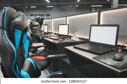 Gaming space with a chair and a laptop in a store technology. Professional equipment for cybersport. Buying a gaming laptop, headphones, mouse and armchairs. Gaming equipment concept.