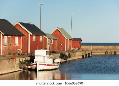 Gammalsby harbor at eastern Oland, Sweden. Small red wooden fishing cabins in a row on the pier with small boats moored dockside in the evening sunlight.