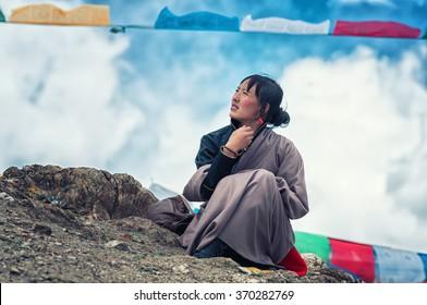 GANDEN, TIBET - APRIL 20: Tibetan woman rests during pilgrimage to the sacred Ganden monastery on 20 April, 2013 in Ganden, Tibet. Ganden monastery is one of the holiest religious sites in Tibet.