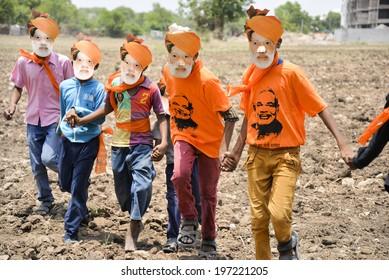GANDHINAGAR, GUJARAT/INDIA - MAY FRIDAY 16  : Boys running infield wearing mask of Narendra Modi on  16 May in BJP office Gandhinagar, India.