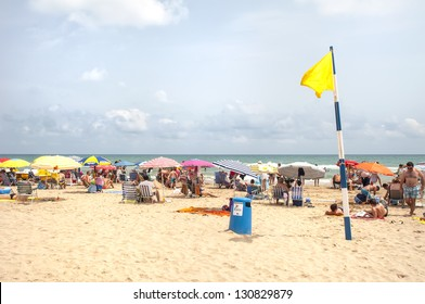 GANDIA,SPAIN-JULY 26: Unidentified people on the beach with yellow caution flag on July 26.2012 in Gandia, Spain. With caution the bathroom is not advisable, either by the sea state