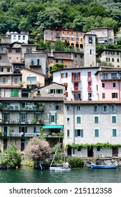 GANDRIA, SWITZERLAND - JULY 5, 2014: Houses and businesses along the shore of Lake Lugano. Buildings nestled into the hillside along the shoreline leading to the town of Gandria.