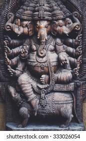 Ganesha god statue. Relief of Ganesha god in dark colors.