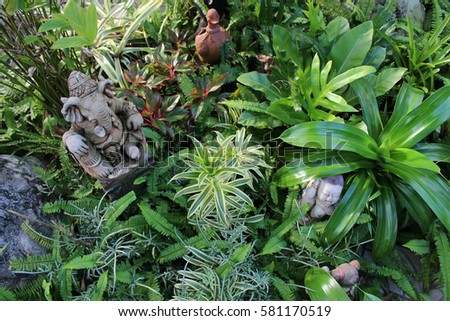 Ganesha And Other Statues Among Thick Tropical Garden Plants