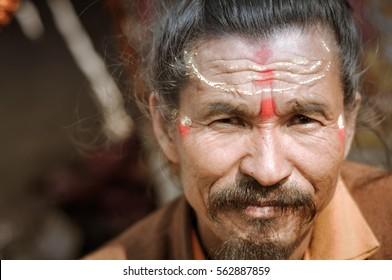 Ganga Sagar, West Bengal - circa January 2012: Older man with red and yellow colour on forehead in Ganga Sagar, West Bengal. Documentary editorial.