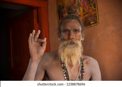 GANGASAGAR, INDIA 14 JANUARY 2018 : Portrait Hindu Sadhu the holy man with  beard, holy white ash applied on body and face, blessing to devotee at Gangasagar.