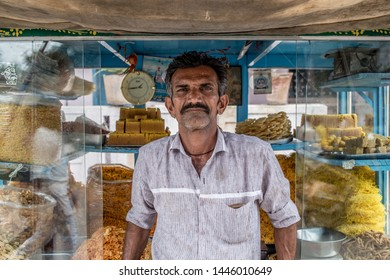 Gangavathi / India - July 8 2019:  Portrait of a Indian man in front of his snacks cart in a south Indian village on a summer afternoon