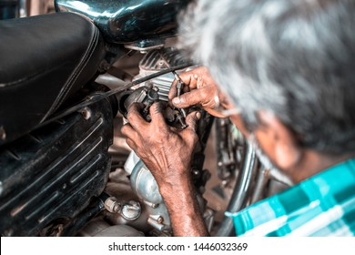 Gangavathi / India - July 8 2019: A mechanic in a small workshop repairing the carburettor on an old motorcycle.