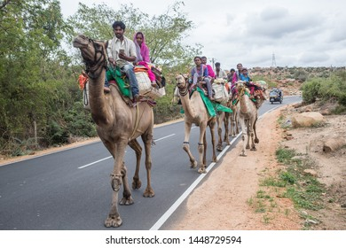 Gangavathi, Karnataka / India - July 11 2019: A group of camel travellers on a road in south India on a cloudy day.