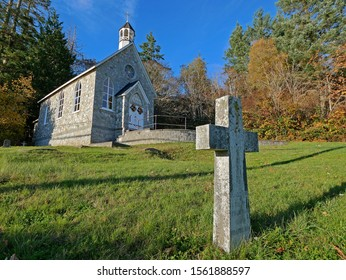 Ganges, Canada - October 27, 2019: A small Catholic church with a tombstone. Taken on Salt Spring Island in Canada, but can illustrate small town life, religion, or places of worship.