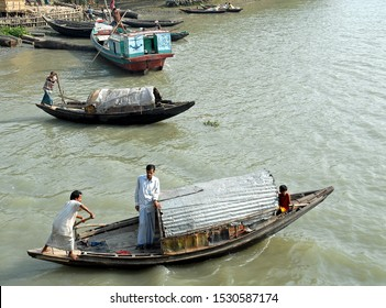 Ganges Delta / Bangladesh - Feb 16 2006: Fishing boats being rowed on the river near a small town. Waterways of the Ganges Delta in southern Bangladesh.