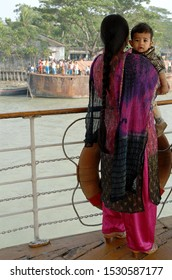 Ganges Delta / Bangladesh - Feb 16 2006: A mother and child standing on the deck of the Rocket paddle steamer as the ship arrives at a small dock. Waterways of the Ganges Delta in southern Bangladesh.