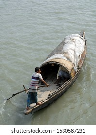 Ganges Delta / Bangladesh - Feb 16 2006: A small fishing boat being rowed on the river in the Ganges Delta. Waterways of the Ganges Delta in southern Bangladesh.