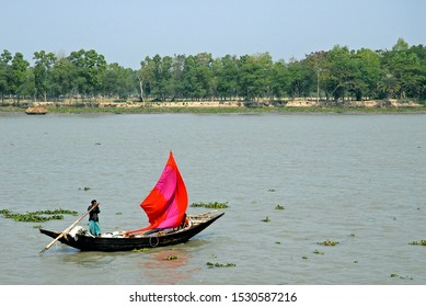 The Ganges Delta in Bangladesh. A small fishing boat with a red sail being rowed on the river in the Ganges Delta. Waterways of the Ganges Delta in southern Bangladesh.