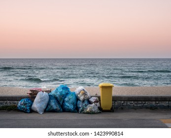 Gangneung, Gangwon Province, South Korea - June 12 2019: A trash heap and trash can on the beach in Sacheon, Gangneung, Gangwon province, South Korea. Sunset sky. Dusk. A rubbish heap and wastebasket.
