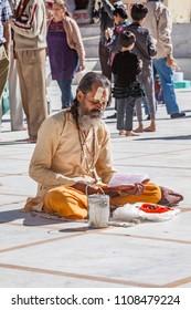 Gangotri, Uttarakhand - CIRCA May 2013 - A Hindu priest sits in the temple courtyard to read Vedic scriptures in Gangotri circa May 2013.