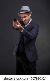 Gangster angry aiming with a gun in hand on a gray background