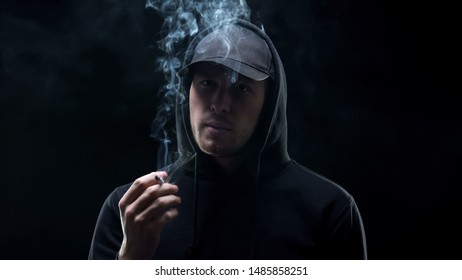 Gangster in black holding cigarette and looking camera, banditry racketeering