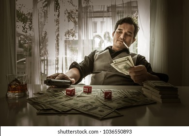 Gangster with bundles of cash, and guns, Bearded male dressed in a suit catch money banknote in the air, Asian mafia gangster with gun and whiskey in hand sitting at table in the safe house