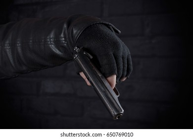 Gangster with a gun in his hand and a leather jacket on a dark background