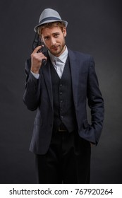 Gangster with a hand in his pocket adjusts his hat with a gun on a gray background