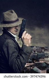 A gangster with hat holding a handgun with a city in the background