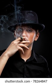 Gangster look. Handsome man with hat and cigar.