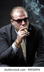 Gangster mafia man in suit with tie and sunglasses looking tough isolated on dark background