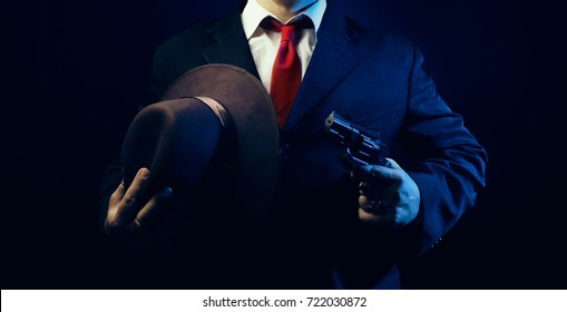 Gangster man in suit. Noir gangster man in suit and red tie holding a brown