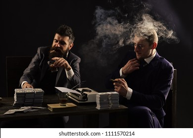 gangster meeting. Illegal business concept. Businessmen discussing illegal deal while drinking and smoking, dark background. Company engaged in illegal business