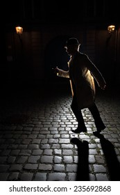 """Gangster wearing a classic trench coat. The man is running on cobblestone with a gun in his hand. The light creates a long shadow towards the viewer. Image inspired by """"film noir"""" movies of the 1940s."""