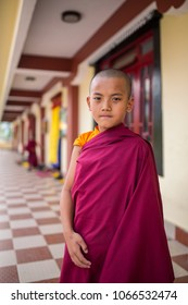 Gangtok, India - May 3, 2017: Unidentified young novice buddhist monk in traditional red robes standing in front of Tsuglakhang monastery in Gangtok, Sikkim, India