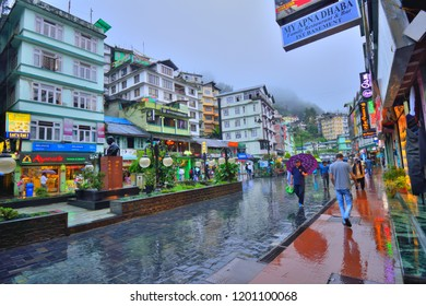 Gangtok, India - September 06, 2018: People walking in the MG Marg street carrying umbrellas during rain.