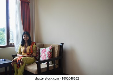 Gangtok, Sikkim, India, 19  October,  2018:  An  Indian lady sitting on a wooden couch near big glass window, selective focusing