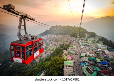 Gangtok,Sikkim - December 13 2017: Tourists enjoy a ropeway cable car/Gondola ride over Gangtok city during sunset. Amazing aerial cityscape of Sikkim. Foggy and golden hour. North east India tourism