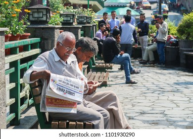 Gangtok,Sikkim/ India - April 14 2018 : Indian old man reading newspaper and group of indian people doing theire morning activity