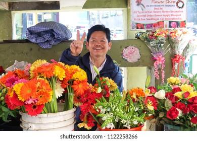 Gangtok,Sikkim/India- April 14,2018 : the flower seller man happy smiling at his flower shop on street Gangtok city, Sikkim.