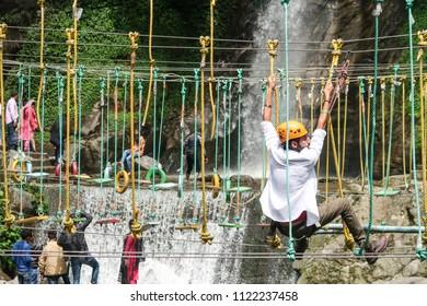 Gangtok,Sikkim/India-April 13,2018 : young Indian man climbling bridge rope  adventure activity at natural waterfall