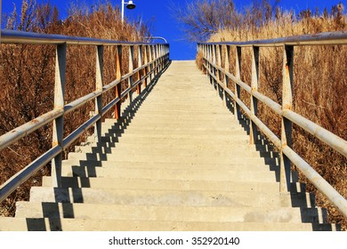 gangway with handrails leading up the hill on a background of dry grass and blue sky