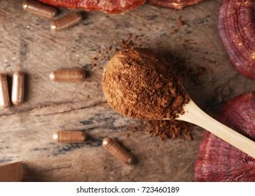 Ganoderma Lucidum powder with copy space on wooden background,Ling Zhi Mushroom.