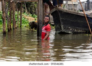 GANVIE, BENIN - JAN 11, 2017: Unidentified Beninese man in the lake Nokwe. Benin people suffer of poverty due to the bad economy.