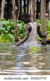 GANVIE, BENIN - JAN 11, 2017: Unidentified Beninese man in the lake Nokwe. Benin people suffer of poverty due to the bad economy.