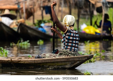 GANVIE, BENIN - JAN 11, 2017: Unidentified Beninese woman sails in a wooden boat over the lake Nokwe. Benin people suffer of poverty due to the bad economy.