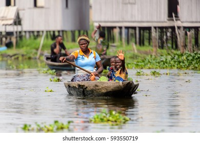 GANVIE, BENIN - JAN 11, 2017: Unidentified Beninese wo with her children sails in a wooden boat in a village over the lake Nokwe. Benin people suffer of poverty due to the bad economy.