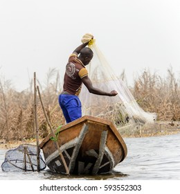 GANVIE, BENIN - JAN 11, 2017: Unidentified Beninese man cathes fish with a net  in a wooden boat in a village over the lake Nokwe. Benin people suffer of poverty due to the bad economy.