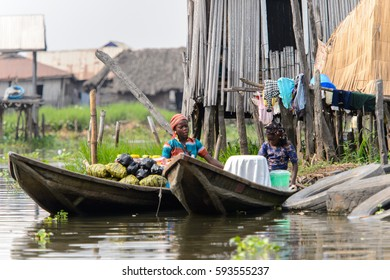 GANVIE, BENIN - JAN 11, 2017: Unidentified Beninese women sail in a wooden boat in a village over the lake Nokwe. Benin people suffer of poverty due to the bad economy.