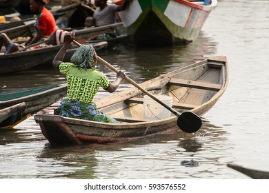 GANVIE, BENIN - JAN 11, 2017: Unidentified Beninese woman in a wooden boat at the port of the lake Nokwe. Benin people suffer of poverty due to the bad economy.