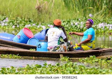 GANVIE, BENIN - JAN 11, 2017: Unidentified Beninese people sails in a wooden boat in a village over the lake Nokwe. Benin people suffer of poverty due to the bad economy.