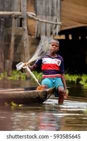 GANVIE, BENIN - JAN 11, 2017: Unidentified Beninese little boy sails in a wooden boat in a village over the lake Nokwe. Benin people suffer of poverty due to the bad economy.