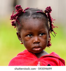 GANVIE, BENIN - JAN 11, 2017: Unidentified Beninese little girl with pigtails in a village over the lake Nokwe. Benin children suffer of poverty due to the bad economy.